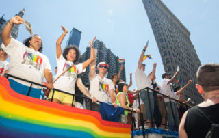 CUNY staff salutes LGBTQ community, celebrating on a wagon at Pride Month